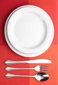 White empty plate with fork, spoon and knife on a red tablecloth — Stock Photo