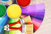 Open tin cans with paint and palette on wooden background — Stock Photo