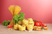 Vermicelli, lettuce and oil on red background — Stock Photo