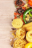 Tasty vermicelli, spaghetti and vegetables on wooden background — Stock Photo