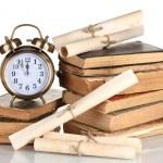 hromadu starých knih s hodinami a posun izolovaných na bílém — Stock fotografie