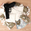 Cocaine and marihuana in packages, dollars and handgun on wooden background - Stock Photo