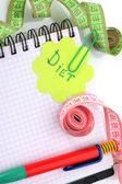 Pianificazione della dieta. nastri di misurazione taccuino e penna isolato su bianco — Foto Stock