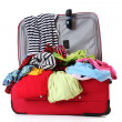 Open red suitcase with clothing isolated on white — Stock Photo