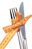 Fork, knife and measuring tape isolated on white — Stock Photo