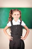Beautiful little girl standing near blackboard in the classroom — Stock Photo