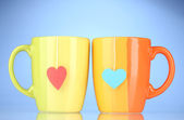 Two cups and tea bags with red and blue heart-shaped label on blue backgrou — Stock Photo