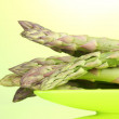 Delicious asparagus on plate on green background — Stock Photo