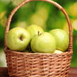 Juicy green apples in basket on wooden table on green background — Stock Photo