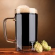 Dark beer in a mug and green hop on wooden table on brown background — Stock Photo #8687151