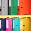 Bright office folders on wooden shelfs on yellow background — Stock Photo