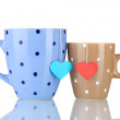 Two cups and tea bags with red and blue heart-shaped label isolated on whit - Stock Photo