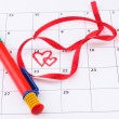 Calendar page with hearts, pen and ribbon on St.Valentines Day — Stock Photo