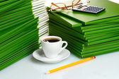 Many green folder with cup of coffee closeup — Stock Photo