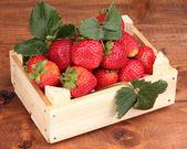Erdbeeren mit blättern in holzkiste auf hölzernen hintergrund — Stockfoto