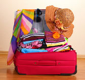 Open red suitcase with clothing in the room — Stock Photo