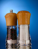 Salt and pepper mills on blue — Stock Photo