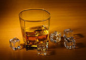 Glass of scotch whiskey and ice on wooden table — Stock Photo