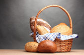 Delicious bread in basket on wooden table on gray background — Stock Photo