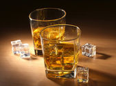 Two glasses of scotch whiskey and ice on wooden table — Stock Photo
