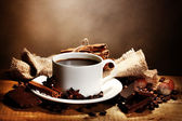 Coffee cup and beans, cinnamon sticks, nuts and chocolate on wooden table o — Stock Photo