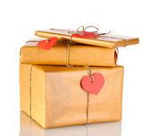 Tre pacchi con etichette a forma di cuore in bianco isolate su bianco — Foto Stock