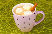 Cup of cappucino with marshmallows and cinnamon on green tablecloth — Stock Photo