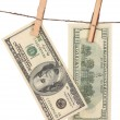 Two one hundred dollar bills is hanging on a rope with wooden clothespin is — Stock Photo