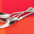 Fork, spoon and knife on a red tablecloth - Stock fotografie
