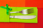 Fork and knife in a green cloth with a bow on a red tablecloth — Stock Photo