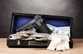 Cocaine, marijuana dollars and handgun in case on wooden table on grey back — Stock Photo