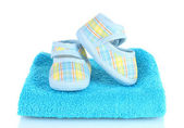 Blue baby booties on blue towel isolated on white — Stock Photo