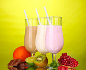 Melk schudt met vruchten en chocolade op groene achtergrond — Stockfoto