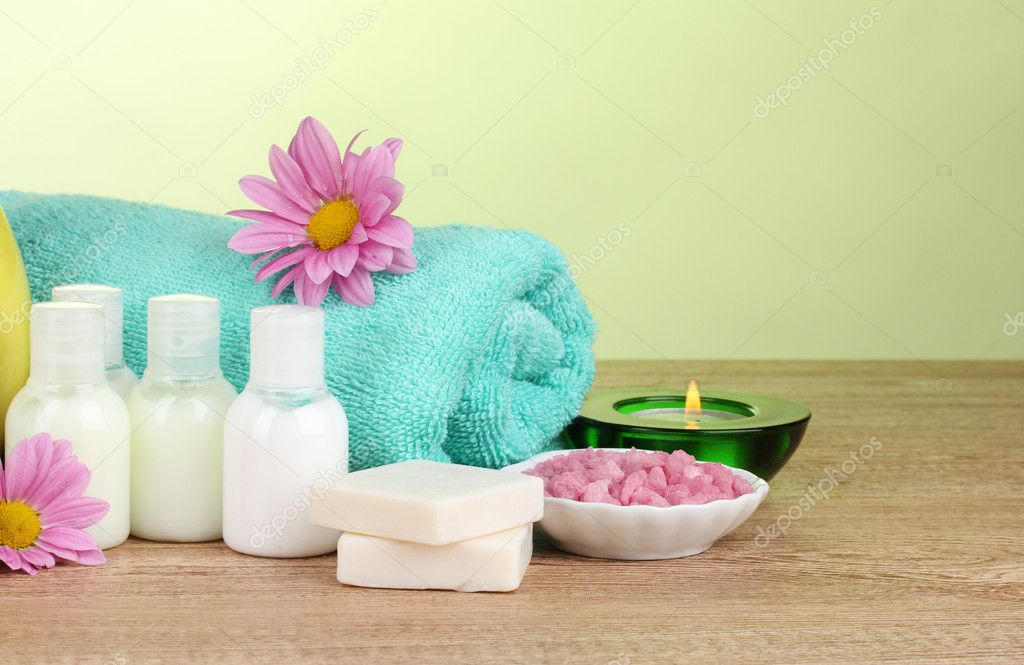 Hotel amenities kit on wooden table on green background — Stock Photo #8749238