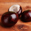 Brown chestnuts on wooden background — Stock Photo