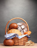 Delicious bread in basket and ears on wooden table on gray background — Stock Photo