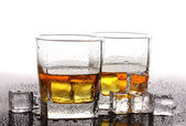 Two glasses of scotch whiskey and ice on table isolated on white — Stock Photo