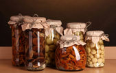 Delicious marinated mushrooms in the glass jars on wooden shelf — Foto Stock