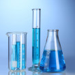 Laboratory glassware with blue liquid with reflection on blue background — Stock Photo #8774637