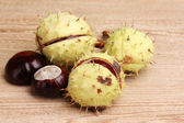 Green and brown chestnuts on wooden background — Stock Photo