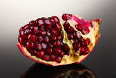 Ripe pomegranate fruit on grey background — Stock fotografie