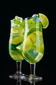Glasses of cocktails with lime and mint on black background — Stock Photo