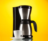 Coffee maker with white cup on yellow background — Stock Photo