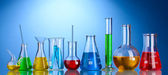 Different laboratory glassware with color liquid and with reflection on blu — Stock Photo