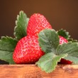 Strawberries with leaves on wooden table on brown  background — Stock Photo