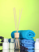 Bottle of air freshener, lavander and towels on green background — Stock Photo