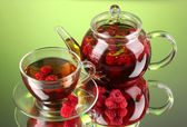 Black fruit raspberry tea in glass teapot and cup on green background — Stock Photo
