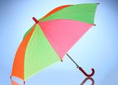 Multi-colored umbrella on blue background — Stock Photo