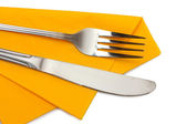Fork and knife in a yellow cloth isolated on white — Stock Photo