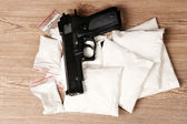 Cocaine in packages and handgun on wooden background — Stock Photo